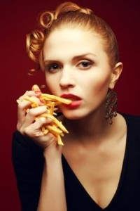 blonde-woman-holding-a-handful-of-french-fries